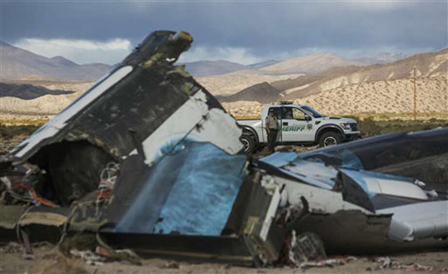 Law enforcement officers keep watch on the wreckage near the site where a Virgin Galactic space tourism rocket, SpaceShipTwo, exploded and crashed in Mojave, Calif. Saturday, Nov 1, 2014. The explosion killed a pilot aboard and seriously injured another while scattering wreckage in Southern California's Mojave Desert, witnesses and officials said. (AP Photo/Ringo H.W. Chiu) Photo: Ringo H.W. Chiu