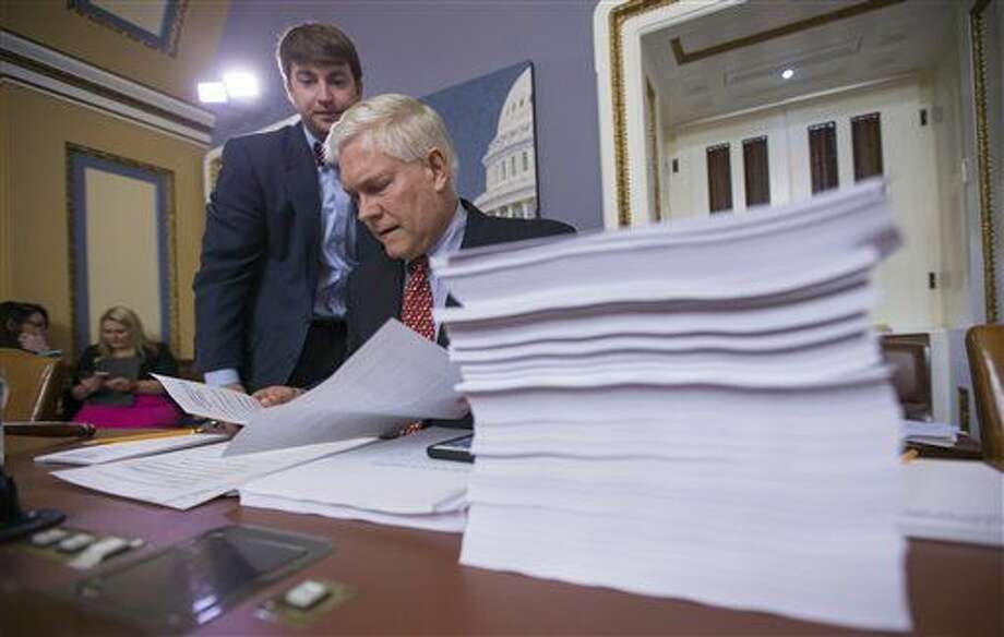 House Rules Committee Chairman Pete Sessions, R-Texas, examines a printout of the $1.1 trillion spending bill to fund the government for the 2016 budget year and extend $680 billion in tax cuts for businesses and individuals, at the Capitol in Washington, Wednesday, Dec. 16, 2015. President Barack Obama is expected to sign the legislation. (AP Photo/J. Scott Applewhite) Photo: J. Scott Applewhite
