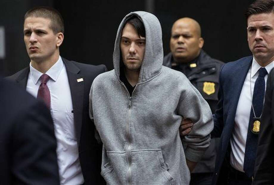 Martin Shkreli, the former hedge fund manager under fire for buying a pharmaceutical company and ratcheting up the price of a life-saving drug, is escorted by law enforcement agents in New York Thursday, Dec. 17, 2015, after being taken into custody following a securities probe. A seven-count indictment unsealed in Brooklyn federal court Thursday charged Shkreli with conspiracy to commit securities fraud, conspiracy to commit wire fraud and securities fraud. (AP Photo/Craig Ruttle) Photo: Craig Ruttle