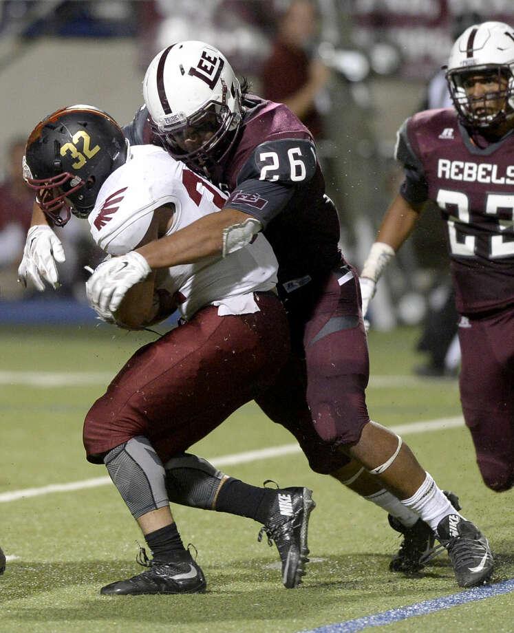 Lee High defensive lineman Kaleb Nunez (26) tackles El Paso El Dorado running back Sergio Gonzalez (32) on Friday, Sept. 18, 2015, at Grande Communications Stadium. James Durbin/Reporter-Telegram Photo: James Durbin