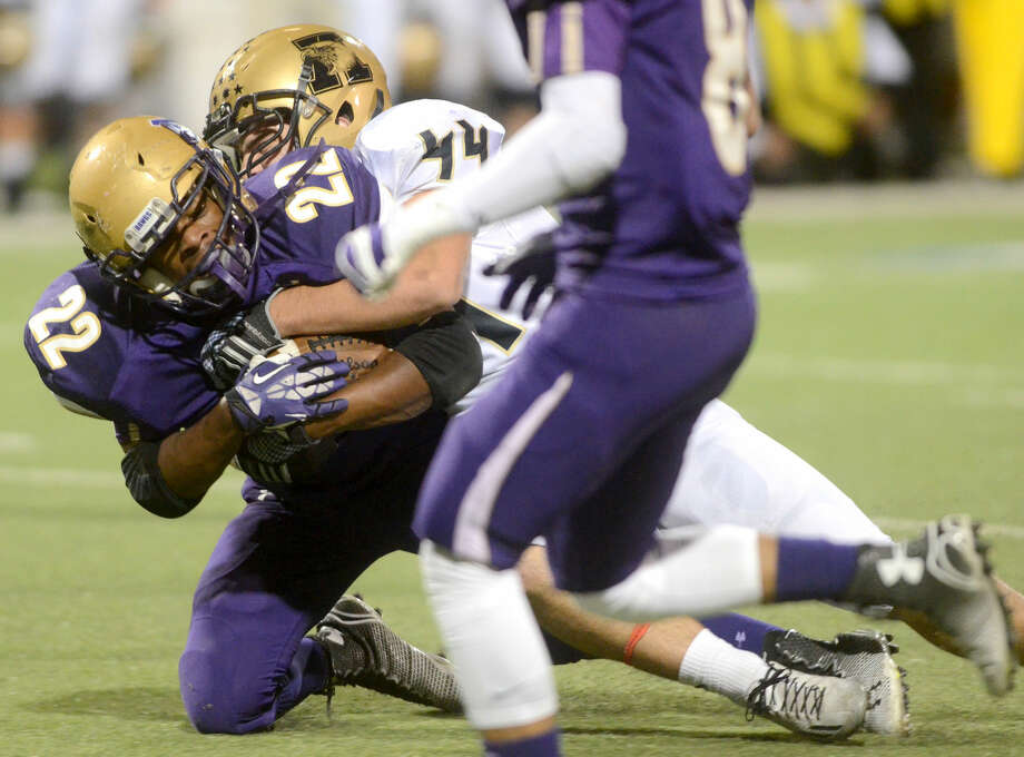 Midland High's Raekwon Anderson (22) is brought down by Abilene High's Dackota Triano (44) on Friday at Grande Communications Stadium. James Durbin/Reporter-Telegram Photo: James Durbin