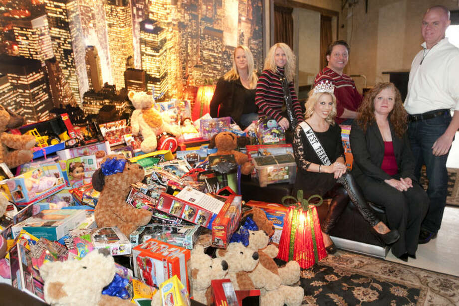 Toy drive volunteers from left, Christy Unrein of Torino's Pizza Bar, Amber Joplin of Rednecks Draft House, Ms. West Texas Shannon Anderson, Steven Palma, founder of Party With A Purpose, Teresa Roumell and Gene Roumell, owner of Rednecks, Torino's and the Boardroom, pose for a photo with a pile of toys for a toy drive on Thursday at the Boardroom. James Durbin/Reporter-Telegram Photo: JAMES DURBIN