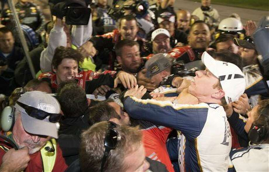 Brad Keselowski, right, is punched during a fight after the NASCAR Sprint Cup Series auto race at Texas Motor Speedway in Fort Worth, Texas, Sunday, Nov. 2, 2014. The crews of Jeff Gordon and Keselowski fought after the race. (AP Photo/Matthew Bishop) Photo: Matthew Bishop