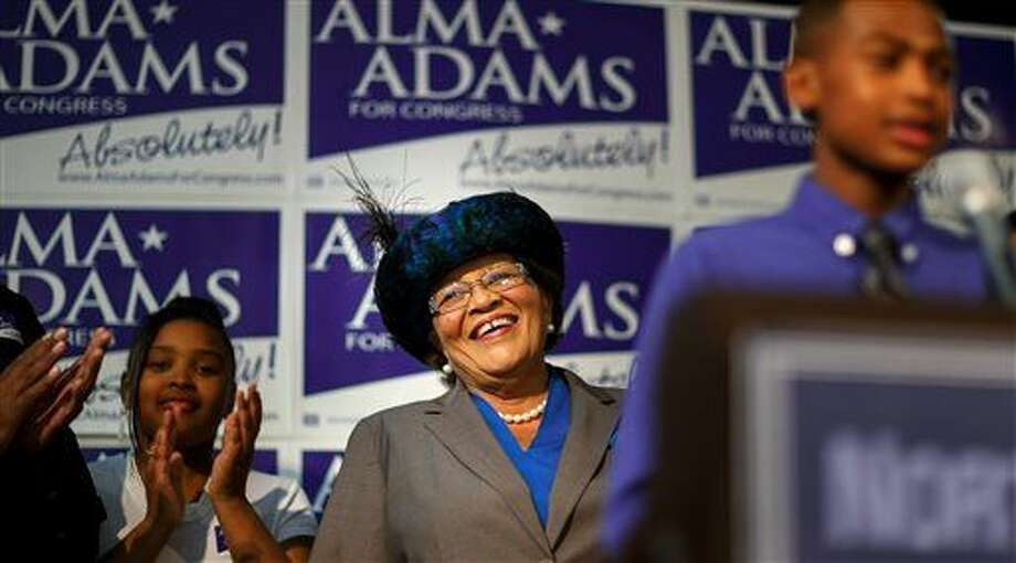 Democrat Alma Adams smiles as her grandson lauds her before she gives her victory speech after winning North Carolina's 12th Congressional District at the Greensboro Coliseum in Greensboro, N.C., on Tuesday, Nov. 4, 2014. (AP Photo/News & Record, Jerry Wolford) Photo: Jerry Wolford