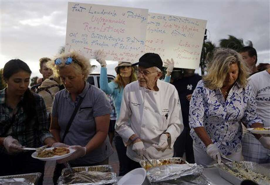 Homeless advocate Arnold Abbott, 90, director of the nonprofit group Love Thy Neighbor Inc., center, serves food to the homeless with the help of volunteers from a public parking lot next to the beach, Wednesday, Nov. 5, 2014, in Fort Lauderdale, Fla. Photo: Lynne Sladky