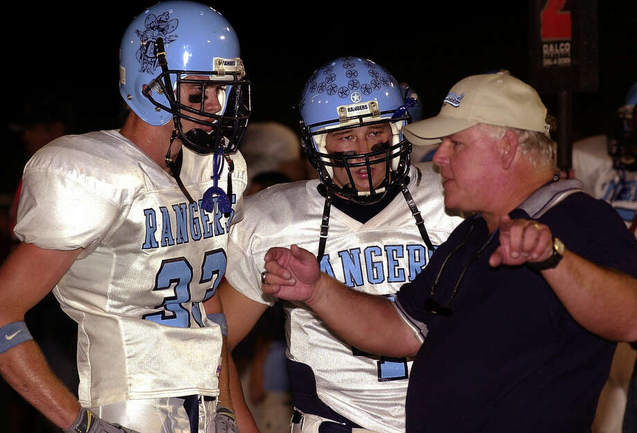 Greenwood coach Bob Purser talks with two of his players Jimmy Brooks, left, and Dawson Wilber during a timeout during the 2002 season at Greenwood.