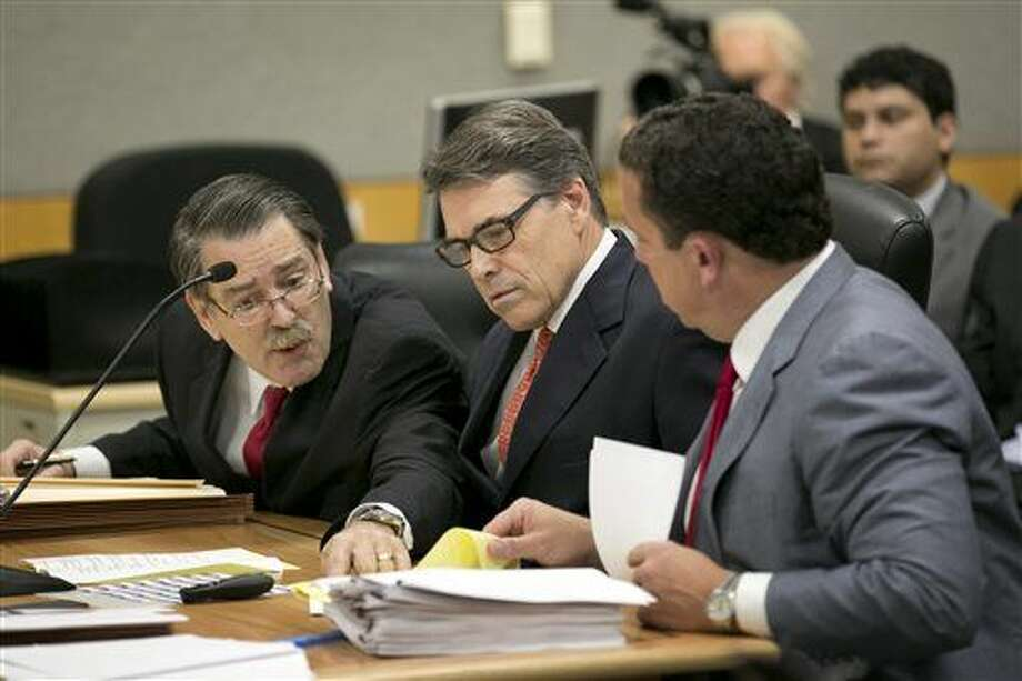 Texas Gov. Rick Perry, center, and his lawyers Tony Buzbee, right, and David Botsford confer during a pretrial hearing on felony abuse of power charges in the 390th District Court at the Blackwell-Thurman Criminal Justice Center, Thursday, Nov. 6, 2014, in Austin, Texas. An Austin grand jury indicted Perry in August. The charges stem from his carrying out a threat to veto state funding for public corruption prosecutors. (AP Photo/Austin American-Statesman, Jay Janner, Pool) Photo: Jay Janner