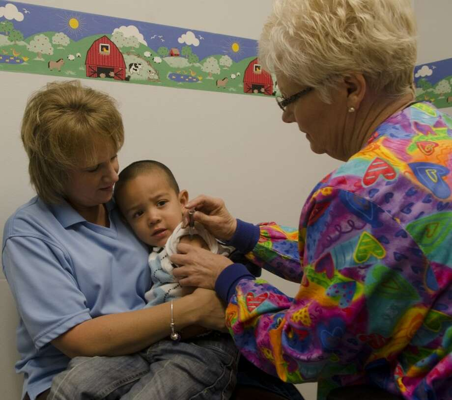 Nursing supervisor Becky Gates, RN, holds Kaleb Villa, 3, as he gets a flu vaccine Monday mornig from Deena Raybon, RN at the Midland Health and Senior Services. Flu vaccines will be available for $15 till the run out at the Midland Health Center. Photo by Tim Fischer/Midland Reporter-Telegram Photo: Tim Fischer