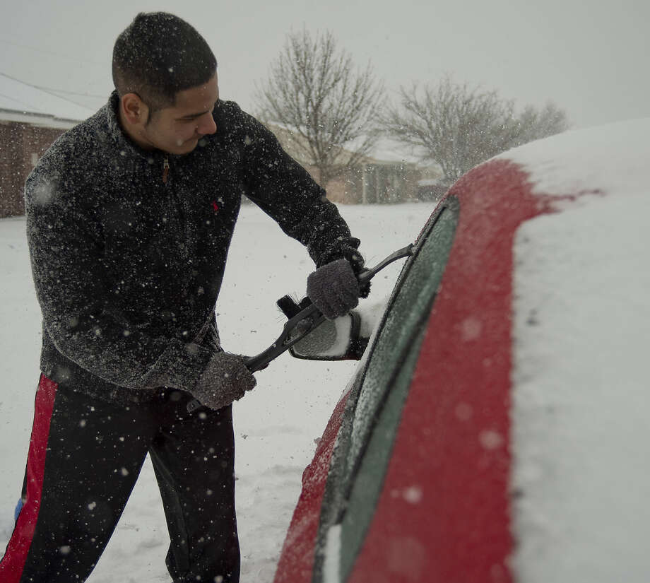 Stefano Petruzziello attempts to scrape ice off his car windows Sunday 12-27-2015 afternoon as snow begins to fall. Tim Fischer\Reporter-Telegram Photo: Tim Fischer