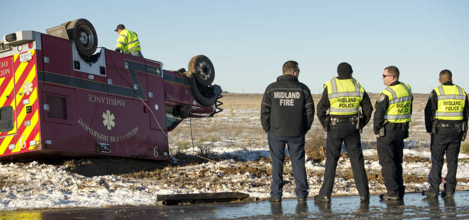 Emergency crews had to rescue one of their own Monday 12-28-2015 after an ambulance, headed to the scene of a travel trailer fire on CR 1278, slid on snow and ice, left the roadway on West CR 60 and rolled over onto the roof. The paramedic driver was the only one in the vehicle and was transported to MMH for observation. Tim Fischer\Reporter-Telegram Photo: Tim Fischer