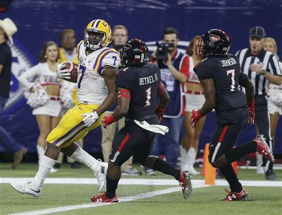 LSU running back Leonard Fournette (7) looks over his shoulder at Texas Tech defensive backs Jah'Shawn Johnson (7) and Nigel Bethel (1) as he scores on a 44-yard touchdown during the first half of the Texas Bowl on Tuesday, Dec. 29, 2015, in Houston. (AP Photo/Bob Levey) Photo: Bob Levey