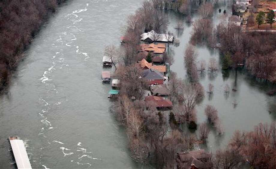 In this Tuesday, Dec. 29, 2015 photo, floodwaters from Lake Taneycomo surrounded several homes in a Branson, Mo., a neighborhood after a record amount of water was released from the Table Rock Lake Dam. (Nathan Papes/The Springfield News-Leader via AP) MANDATORY CREDIT Photo: Nathan Papes