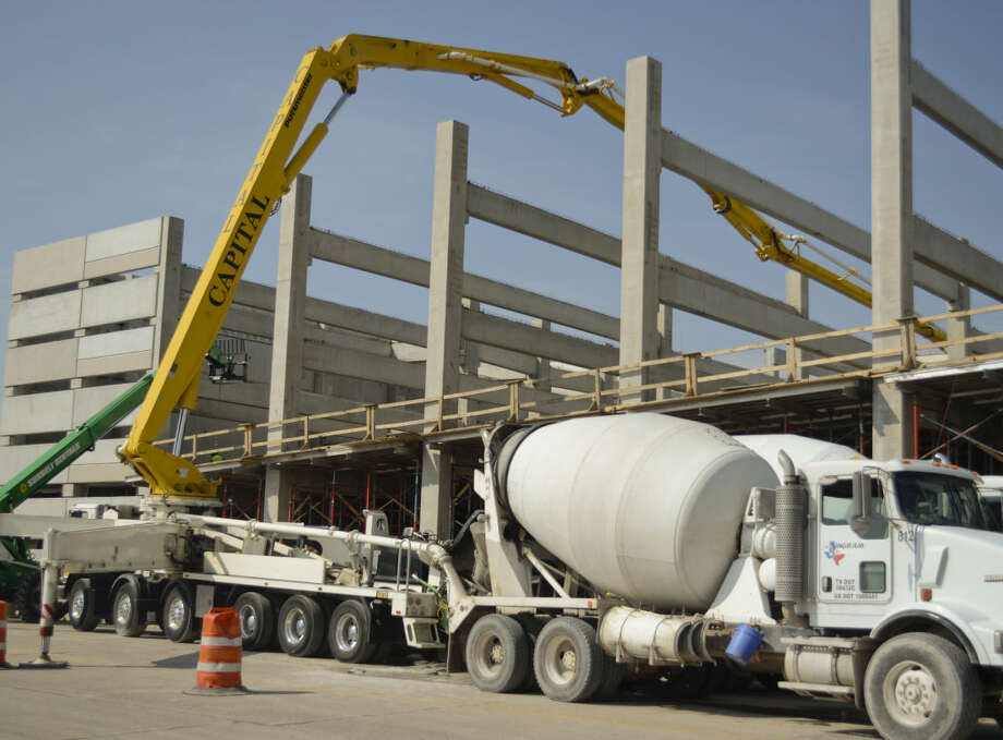 Workers use a concrete boom pump truck to move concrete to upper floors of the parking garage for Wall Street Lofts Tuesday morning. Tim Fischer\Reporter-Telegram Photo: Tim Fischer