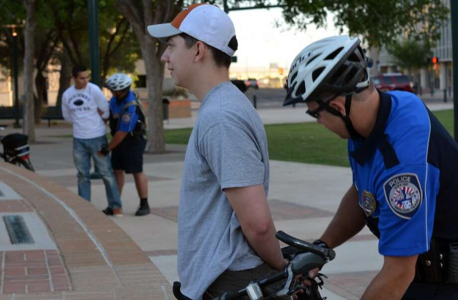 Officer Kyle Wegner arrests Midland Police Department Explorer Angelo Subia during department bike training Tuesday evening at the Centennial Plaza. The MPD Explorers, high school students who are studying to become police officers, participate in the neighborhood patrol phase of the MPD training. The officers also must go through an extensive bicycle circuit throughout the city and a written test before becoming certified. Photo: James Cannon/MRT