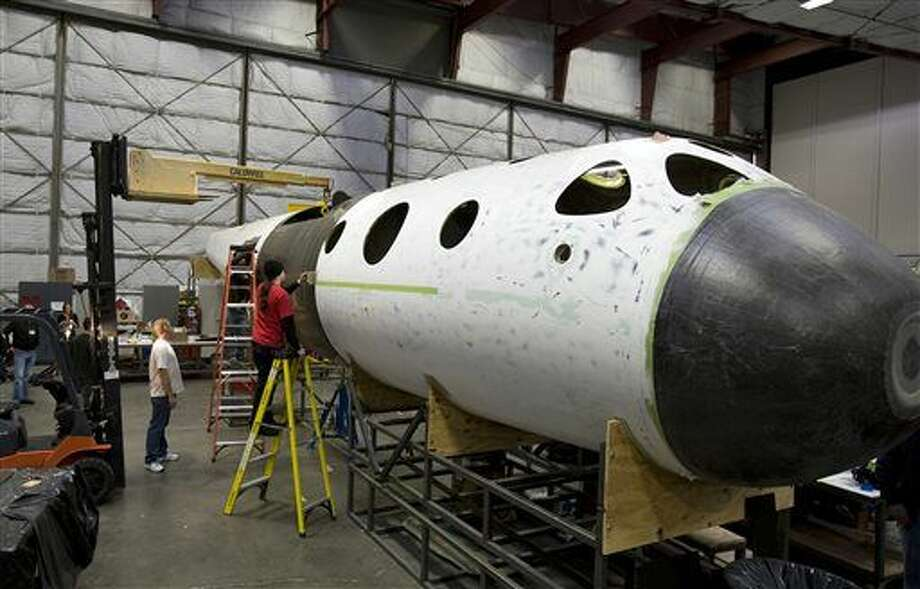 FILE - This undated file photo, first released in 2008 by Virgin Galactic, shows SpaceShipTwo's construction inside the Scaled Composites plant at the Mojave Airport in Mojave, Calif. The head of the space tourism company that suffered a tragic setback when its experimental rocket ship broke apart over the California desert says test flights could resume as early as next summer. Virgin Galactic CEO George Whitesides told The Associated Press on Wednesday, Nov. 5, 2014 that work is underway at the company's Mojave shop to finish a second spacecraft. It will replace the first SpaceShipTwo, which was destroyed last week when it disintegrated during a test flight, killing one pilot and seriously injuring another.(AP Photo/Virgin Galactic, File) NO SLALES Photo: HONS