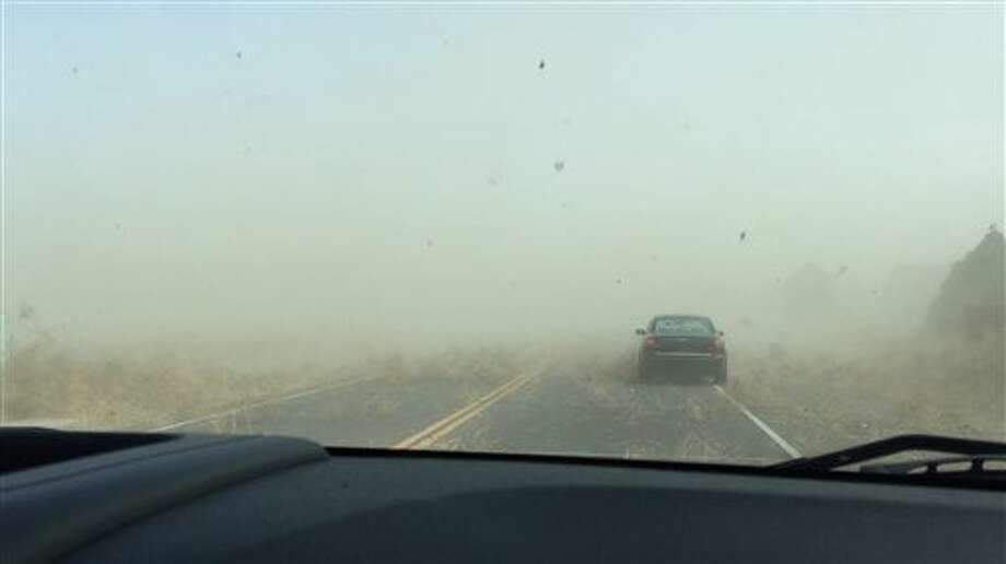 This photograph provided by Brian Paulson shows a dust storm carrying tumbleweeds on the road near Pueblo West, south of Colorado Springs, Colo., Tuesday, Nov. 11, 2014. The arctic air mass affecting the central United States and Rockies kicked up tumbleweeds and dust as it blew across Colorado. (AP Photo/Brian Paulson) Photo: Brian Paulson