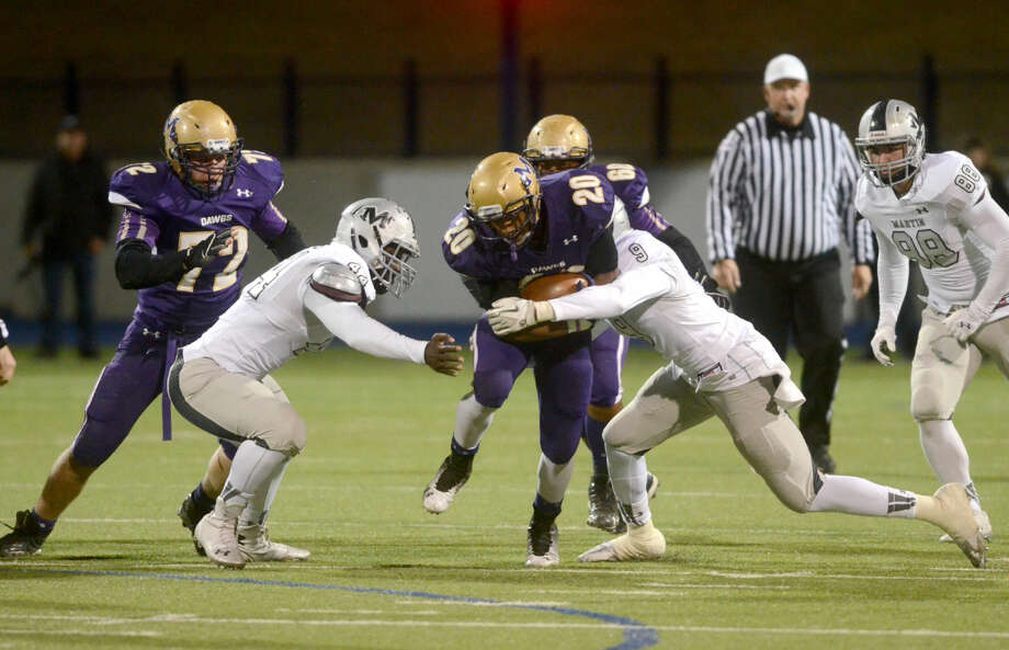 Midland High's Ricky Hubert (20) is brought down by Arlington Martin's DD Fletcher (44) and Damarcus Bowers (9) on Friday at Grande Communications Stadium. James Durbin/Reporter-Telegram Photo: James Durbin