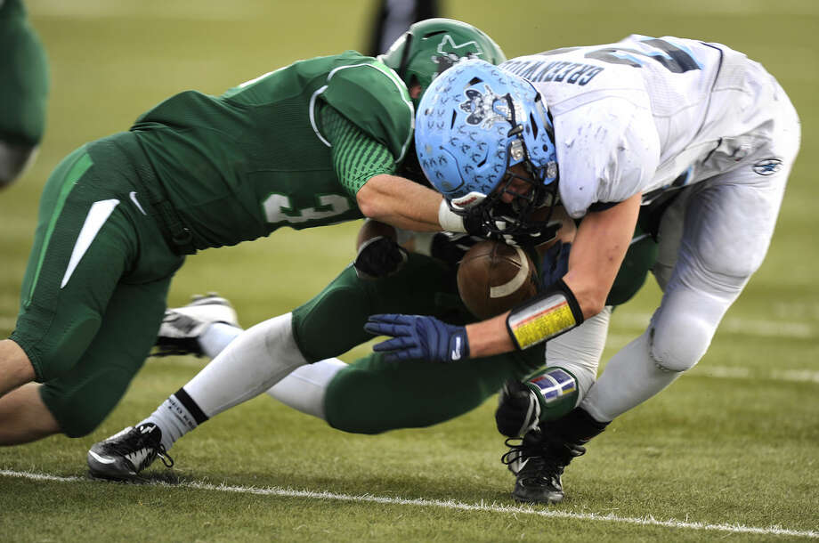 Midland Greenwood running back Jake Rogers (23) fumbles the ball while being hit by a pair of Iowa Park defenders during the third quarter of Greenwood's 35-20 loss in the Region I-4A Div. II bi-district playoff on Saturday, Nov. 15, 2014, at Bulldog Stadium in Abilene. Thomas Metthe/Reporter-News Photo: Thomas Metthe