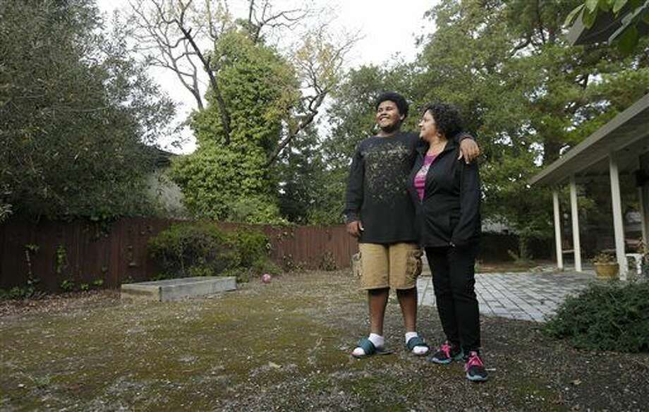 FOR RELEASE AT 12:01 A.M. EST ON MONDAY, NOV. 17. THIS PHOTO MAY NOT BE PUBLISHED, BROADCAST OR POSTED ONLINE BEFORE 12:01 A.M. EST - In this Nov. 13, 2014 photo, Gina Cooper, right, and her son Dante Walton, 14, pose for photos at their home in San Carlos, Calif. After a few months as nomads in 2012 when Cooper and Walton, then 12, had to vacate their home when her salary became insufficient to pay the rent, they found shelter and support with an interfaith program and stayed there five months before Cooper saved enough to be able to afford housing on her own. (AP Photo/Jeff Chiu) Photo: Jeff Chiu