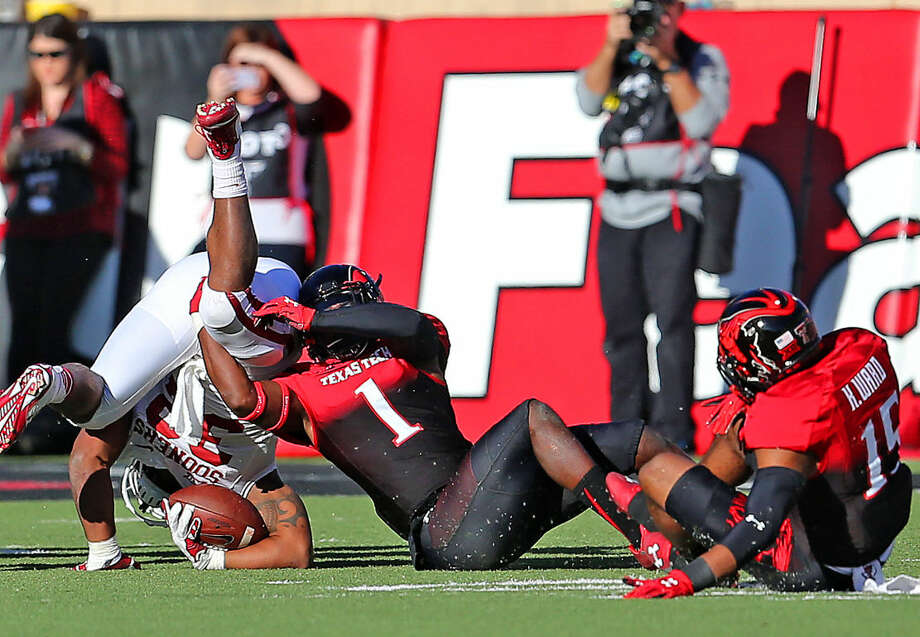 Texas Tech defensive back NigelBethel II upends Oklahoma running back Samaje Perine (32) in Saturday's Big XII action at Jones AT&T Stadium. Photo: Wade H Clay