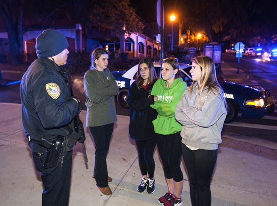 A Tallahassee police officer talks to several students outside the Strozier library on the Florida State University campus in Tallahassee, Fla., where a shooting occurred early Thursday morning. The gunman, reportedly a Texas Tech law school graduate, was shot and killed by police. Photo: Associated Press