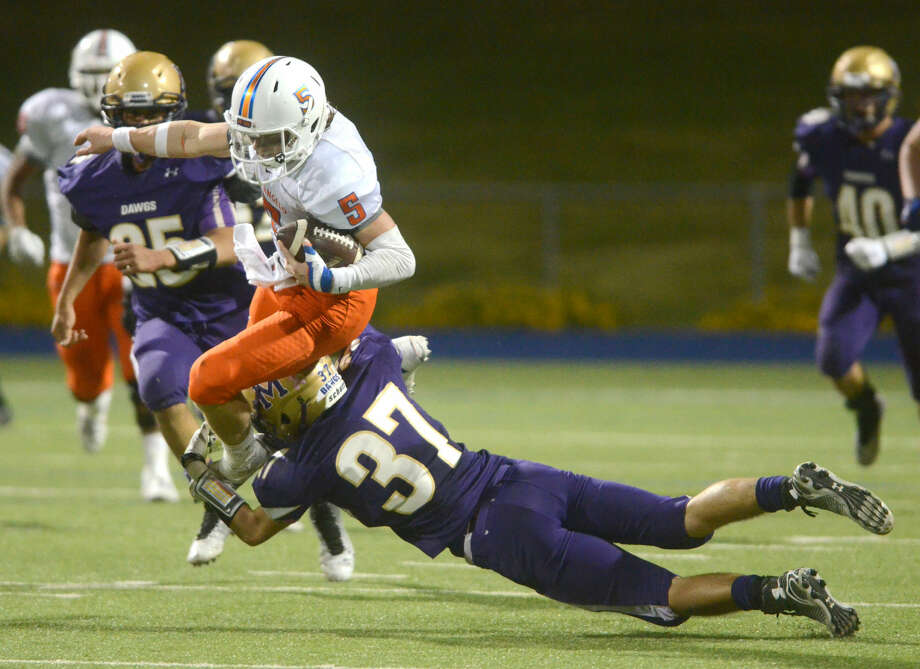 San Angelo Central quarterback Braden Hucks jumps over a tackle from Midland High's Blake Humble (37) on Friday at Midland High. James Durbin/Reporter-Telegram Photo: James Durbin