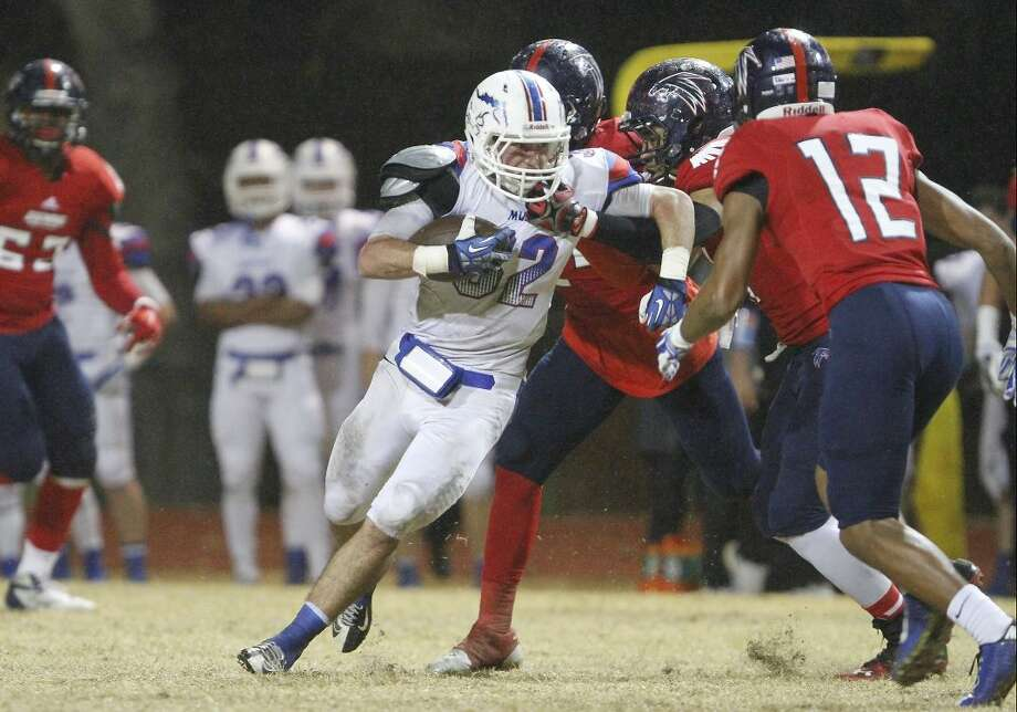 21 November 2014: Midland Christian running back Justin Fender #32 tries to escape from a tackle during the game between the Midland Christian Mustangs and the Bishop Dunne Falcons at Bishop Dunne Stadium in Dallas, Texas. Bishop beat Midland 41-14.