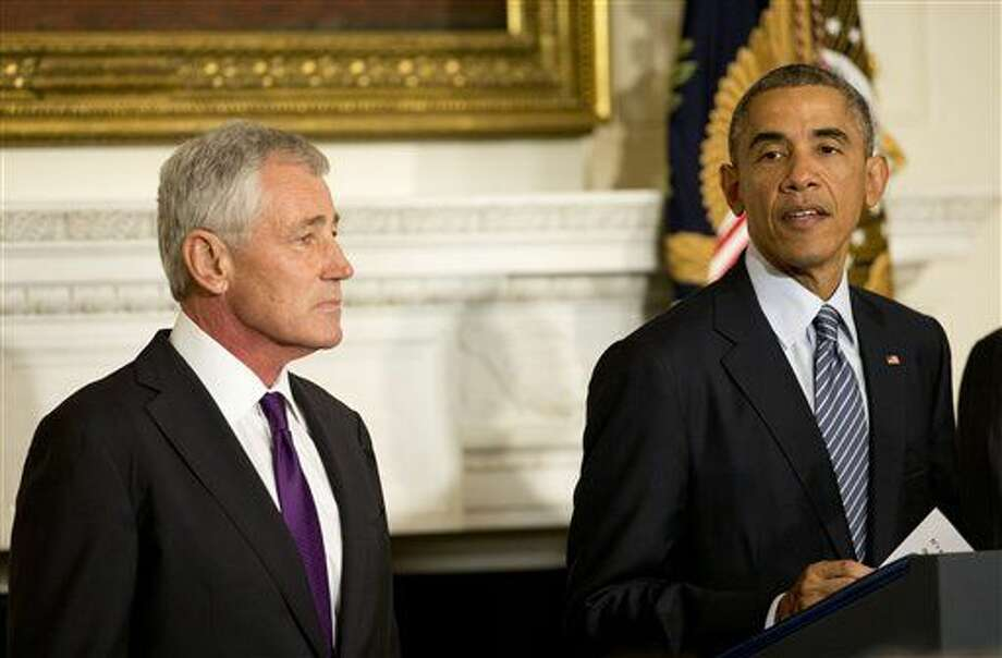 President Barack Obama, standing with Defense Secretary Chuck Hagel, talks about Hagel's resignation during an event in the State Dining Room of the White House in Washington, Monday, Nov. 24, 2014. Hagel is stepping down under pressure from Obama's Cabinet, senior administration officials said Monday, following a tenure in which he has struggled to break through the White House's insular foreign policy team. (AP Photo/Pablo Martinez Monsivais) Photo: Pablo Martinez Monsivais