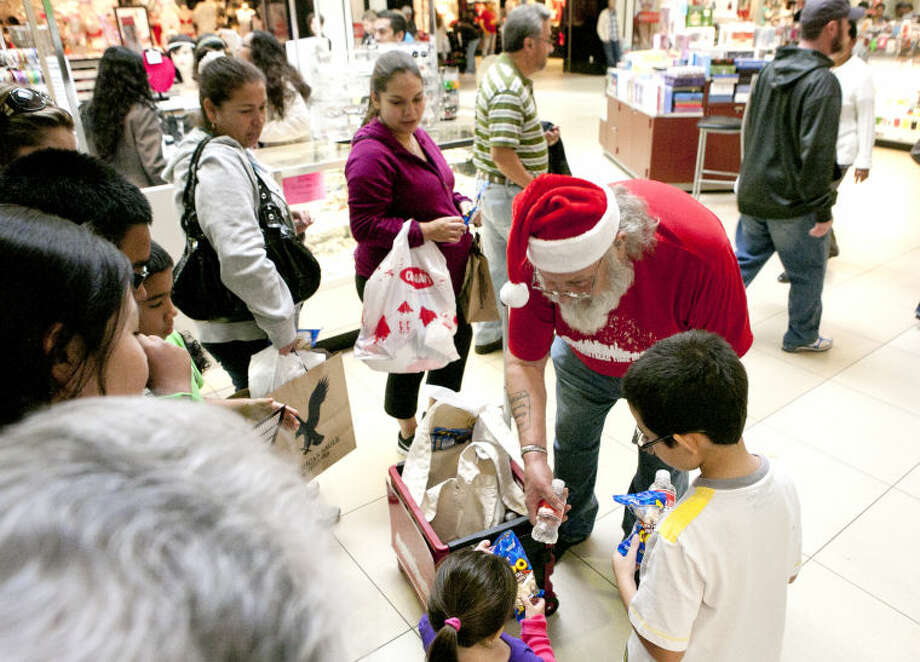 James Lawrence, a volunteer from Stonegate Fellowship Church, hands out water and animal crackers to shoppers at Midland Park Mall on Friday. James Durbin/Reporter-Telegram Photo: JAMES DURBIN