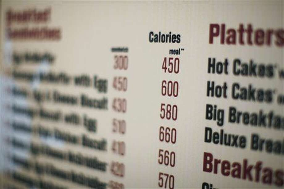 In this July 18, 2008 file photo, calories of each food item appear on a McDonalds drive-thru menu in New York. Companies will have until November 2015 to comply. (AP Photo/Ed Ou, File) Photo: ED OU