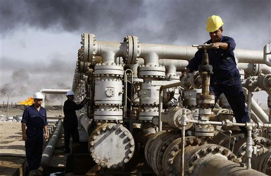 FILE - In this Dec. 13, 2009, file photo, oil personnel work at the Rumaila oil refinery, near the city of Basra, Iraq. (AP Photo/Nabil al-Jurani, File) Photo: Nabil Al-Jurani