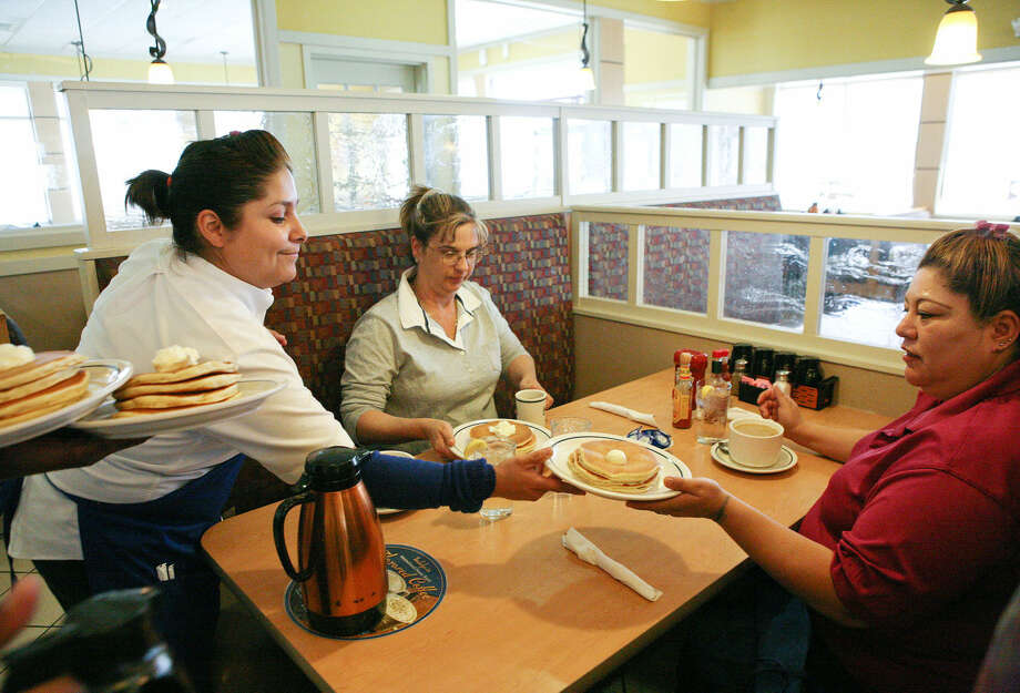 Sylvia Sypia serves a free helping of buttermilk pancakes to Lori McClain, left, and Norma Arrendondo during IHOP's annual free pancake day to benefit the network of children's hospitals. IHOP will remain open on Thanksgiving Day. Photo: Cindeka Nealy