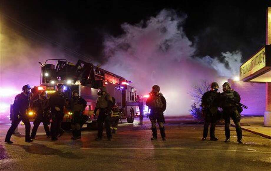 Smoke fills the streets as some buildings are on fire after the announcement of the grand jury decision Monday, Nov. 24, 2014, in Ferguson, Mo. Photo: Jeff Roberson