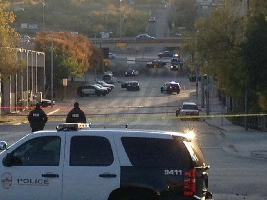 Police tape marks off the scene after authorities shot and killed a man who they say opened fire on the Mexican Consulate, police headquarters and other downtown buildings early Friday, Nov. 28, 2014, in Austin, Texas. In the distance, police cars surround the suspect's vehicle parked near the Interstate 35 overpass. (AP Photo/Jim Vertuno) Photo: Jim Vertuno