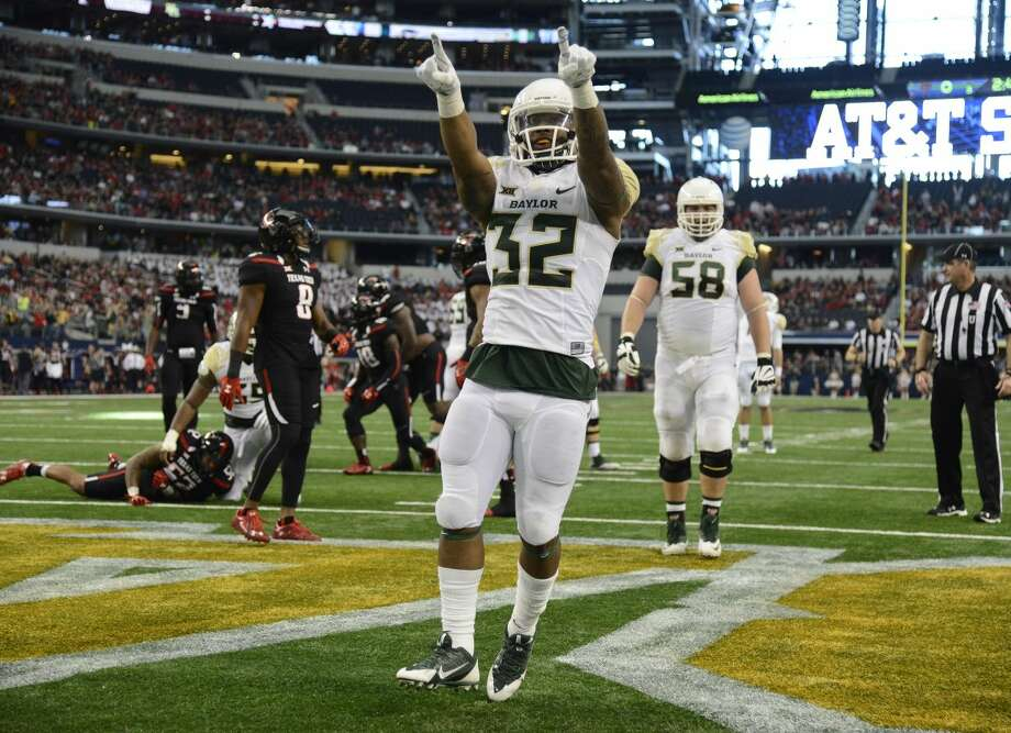 CORRECTS DATE - Baylor running back Shock Linwood (32) points to the stands after scoring a touchdown against Texas Tech in the first half of an NCAA college football game, Saturday, Nov. 29, 2014, in Arlington, Texas. (AP Photo/Tim Sharp) Photo: TIM SHARP
