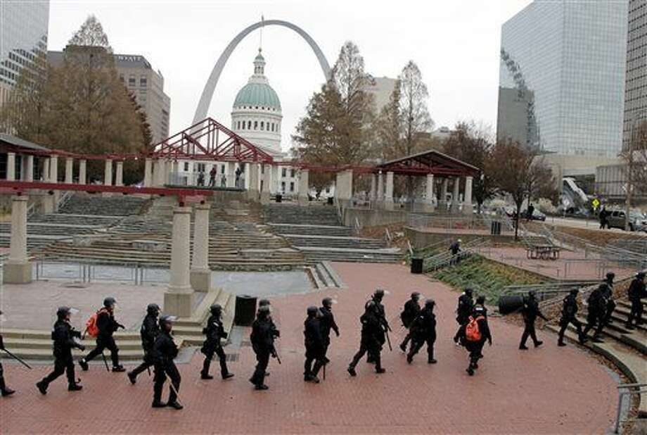 Officers wearing riot gear walk through a park Sunday, Nov. 30, 2014, in downtown St. Louis. Police and protesters clashed after an NFL football game between the St. Louis Rams and the Oakland Raiders as protests continued following a grand jury's decision not to indict a Ferguson police officer in the shooting death of Michael Brown. (AP Photo/Tom Gannam) Photo: Tom Gannam