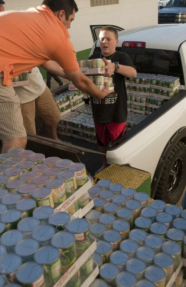 Garrett Whitehill, 11, hands one of the cases of food to his step-dad Cody Crossland, as they help unload the tons of food Whitehill collected for the West Texas Food Bank. Tim Fischer\Reporter-Telegram Photo: Tim Fischer