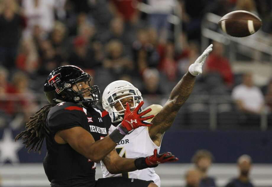 Texas Tech wide receiver Bradley Marquez, left, waits for the ball to make a touchdown catch against Baylor cornerback Xavien Howard (4) in the second half of an NCAA college football game, Saturday, Nov. 29, 2014, in Arlington, Texas. Baylor won the game 48-46. (AP Photo/Tim Sharp) Photo: TIM SHARP