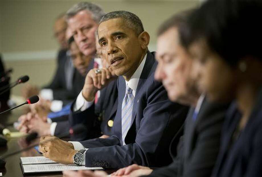 President Barack Obama, center, speaks during his meeting with elected officials, law enforcement officials and community and faith leaders in the Old Executive Office Building on the White House Complex in Washington, Monday, Dec. 1, 2014. Obama said that in the wake of the shooting of an unarmed 18-year-old man in Ferguson, Missouri, he wants to make sure to build better trust between police and the communities they serve.(AP Photo/Pablo Martinez Monsivais) Photo: Pablo Martinez Monsivais