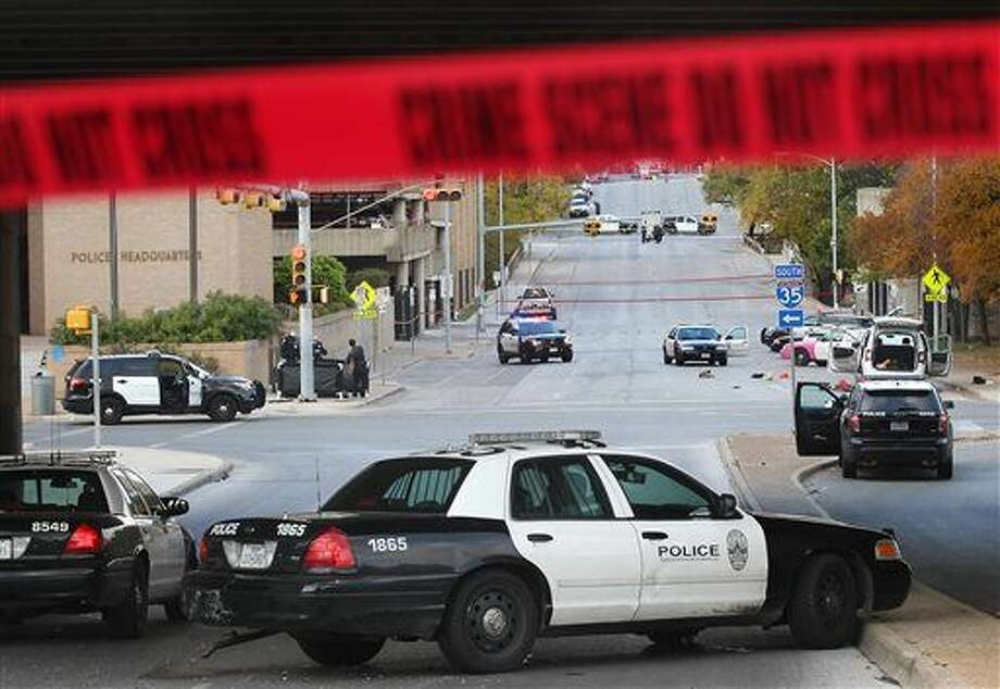 Police arrive on the scene after authorities shot and killed a man who they say opened fire on the Mexican Consulate, police headquarters and other downtown buildings early Friday, Nov. 28, 2014, in Austin, Texas. The gunman fired more than 100 rounds at downtown buildings early Friday before he died, Austin authorities said. (AP Photo/Austin American-Statesman, Laura Skelding) AUSTIN CHRONICLE OUT, COMMUNITY IMPACT OUT, INTERNET AND TV MUST CREDIT PHOTOGRAPHER AND STATESMAN.COM, MAGS OUT Photo: Laura Skelding