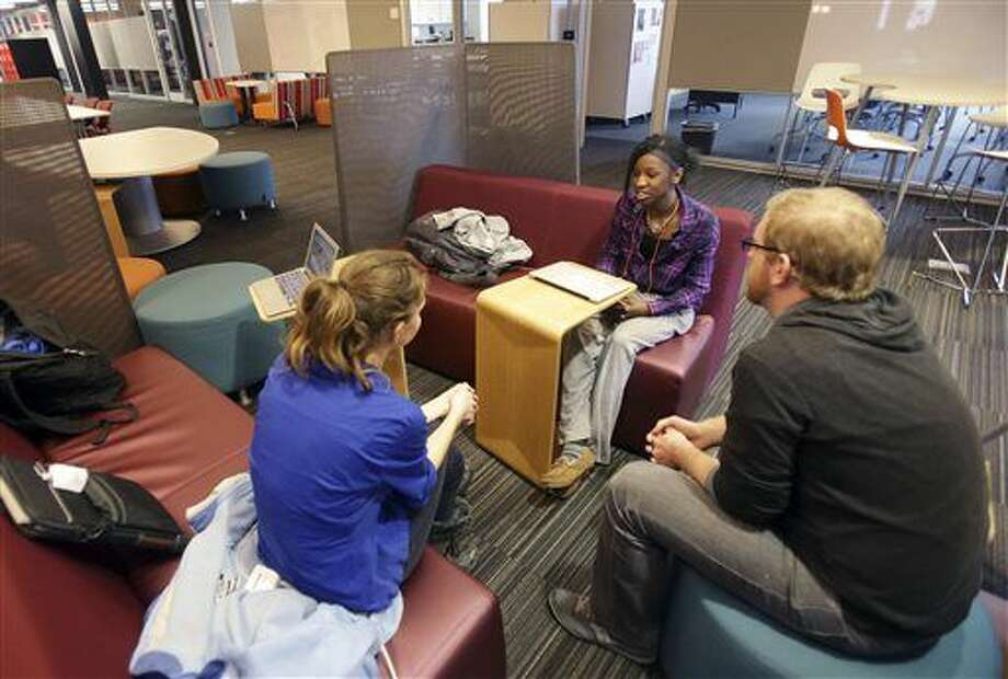 English teacher Tom Rademacher, right, talks with his high school juniors Kierra Murray, right, and Ana Silverman, left, Tuesday, Dec. 2, 2014, at Fair School in Minneapolis about the situation in Ferguson. Knowing that the grand jury decision not to indict a white officer who shot and killed a black teen in Ferguson, Mo., would be on the minds of his students, Rademacher put aside his lesson plans and asked them a question: How did they feel? (AP Photo/Jim Mone) Photo: Jim Mone