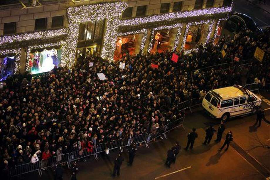 A group of protesters with signs, rear, rally against the decision not to indict the police officer involved in the death of Eric Garner as they mix with spectators near Rockefeller Center during a ceremony to light the Rockefeller Center Christmas Tree, Wednesday, Dec. 3, 2014, in New York. (AP Photo/Jason DeCrow) Photo: Jason DeCrow