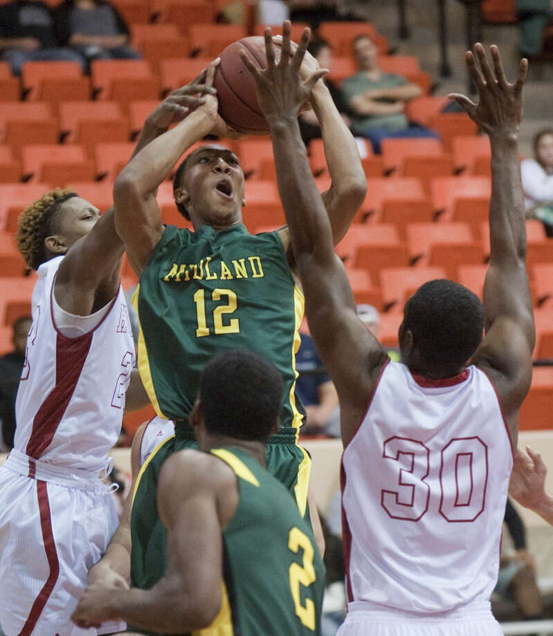 Midland College's Bryce Ervin puts up a shot between Howard College's Travis Charles, 30 and Lis Shoshi Wednesday evening at Dorothy Garrett Coliseum. Tim Fischer\Reporter-Telegram Photo: Tim Fischer