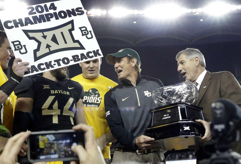 Big 12 Commissioner Bob Bowlsby, right, presents Baylor head coach Art Briles, center, with the conference trophy after their 38-27 win over Kansas State in an NCAA college football game, Saturday, Dec. 6, 2014, in Waco, Texas. (AP Photo/Tony Gutierrez) Photo: Tony Gutierrez