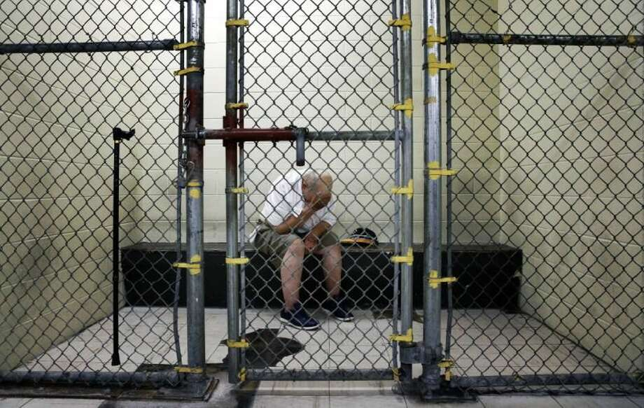 In this June 26, 2014 photo, a U.S. veteran with post-traumatic stress sits in a segregated holding pen at the Cook County Jail after he was arrested on a narcotics charge in Chicago. From big cities to rural counties, the nation's 3,300 local jails have turned into treatment centers of last resort for people with serious mental illnesses, most arrested for non-violent crimes. Photo: Associated Press