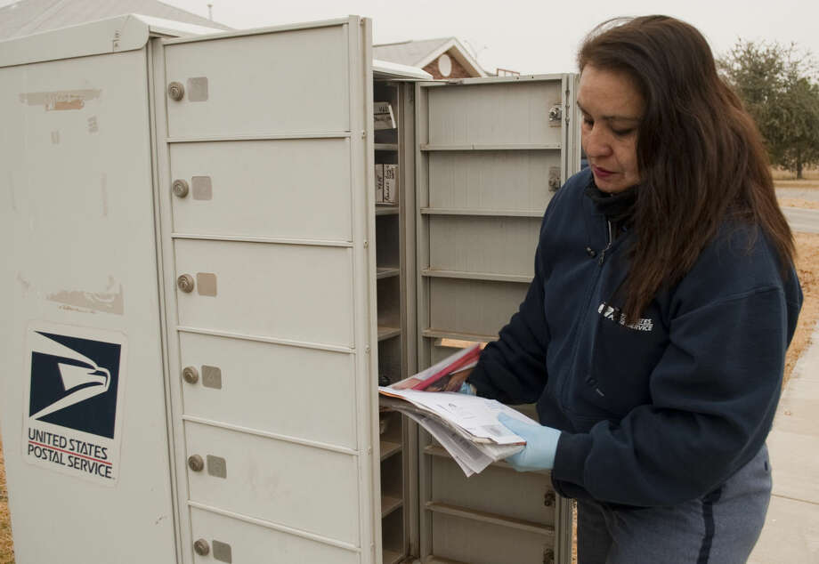 Nancy Turner, a 30-year U.S. Postal Service employee, delivers mail Tuesday morning. In addition to their regular routes, carriers are delivering packages for Amazon.Tim Fischer/Reporter-Telegram Photo: Tim Fischer