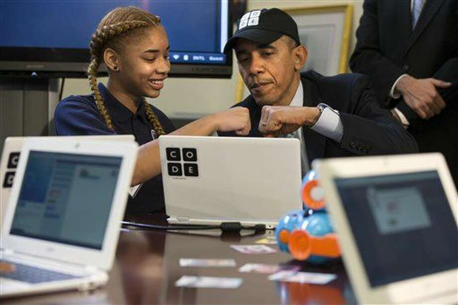 "President Barack Obama does a ""fist bump"" with a Adrianna Mitchell during an ""Hour of Code"" event in the Eisenhower Executive Office Building on the White House complex in Washington, Monday, Dec. 8, 2014, attended by middle-school students from Newark, N.J. (AP Photo/Jacquelyn Martin) Photo: Jacquelyn Martin"