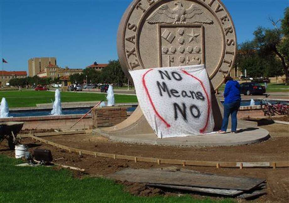"FILE - In this Oct. 1, 2014 file photo, Texas Tech freshman Regan Elder helps drape a bed sheet with the message "" No means No"" over the university's seal on the campus in Lubbock, Texas. A task force on Greek culture at the university campus says in an interim report released Wednesday, Dec. 10, 2014, that there are numerous areas lacking in oversight and regulation of fraternities and their activities. The task force was formed by the university's president and the system's chancellor after pictures taken at a fraternity party showed a banner that read, ""No means yes, yes means anal (sex)."" (AP Photo/Betsy Blaney, File) Photo: Betsy Blaney"