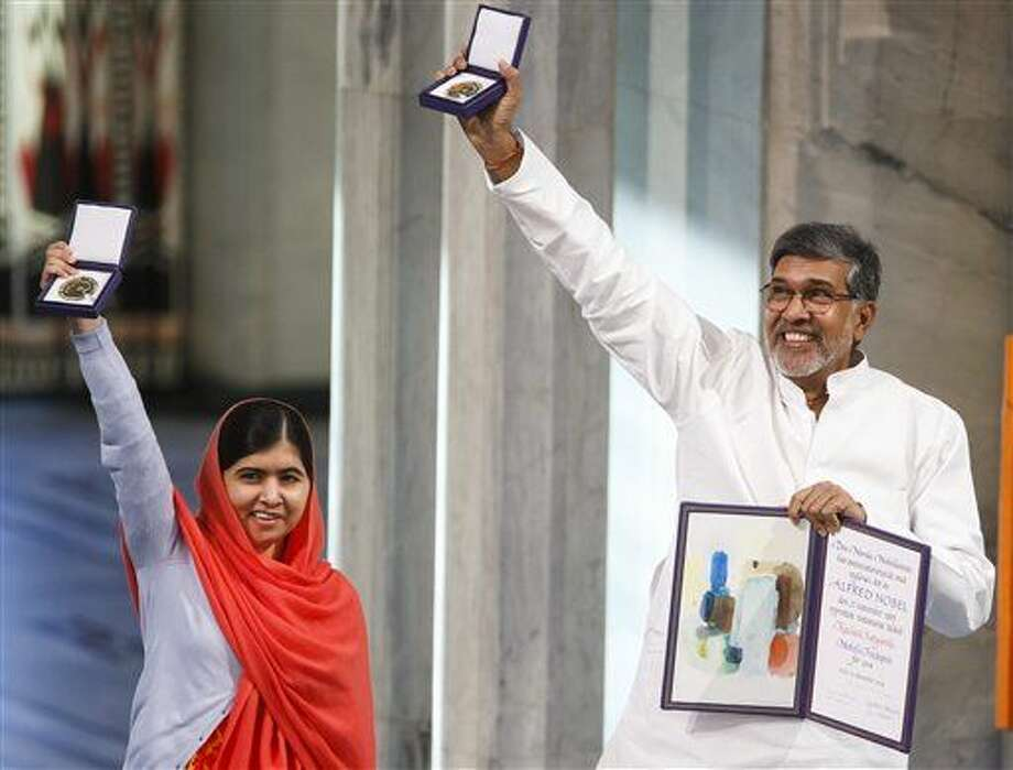 Nobel Peace Prize winners Malala Yousafzai from Pakistan and Kailash Satyarthi of India hold up their Nobel Peace Prize medals during the Nobel Peace Prize award ceremony in Oslo, Norway, Wednesday, Dec. 10, 2014. The Nobel Peace Prize is being shared between Malala Yousafzai, the 17-year-old Taliban attack survivor, and the youngest Nobel Prize winner ever, and Indian children's rights activist Kailash Satyarthi in a ceremony in Oslo on Wednesday. (AP Photo/Heiko Junge, NTB Scanpix) NORWAY OUT Photo: Heiko Junge