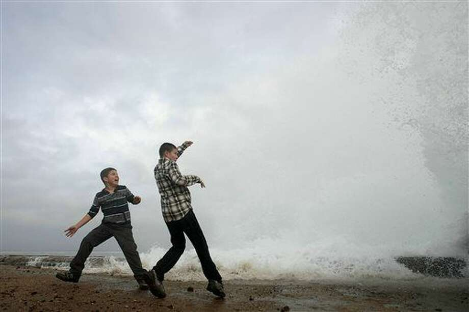 Aidan Stephenson,12, and Conor Stephenson,10, visiting from Phoenix, watch the waves breaking on the rocks on Ocean View Blvd., Wednesday, Dec.10, 2014, in Pacific Grove, Calif. Northern California residents are bracing for a powerful storm that could be the biggest in five years and which prompted the National Weather Service to issue a high wind and flash flood warning. The storm is expected to arrive Wednesday and pelt the region through Thursday. (AP Photo/Monterey Herald, Vern Fisher) Photo: Vern Fisher